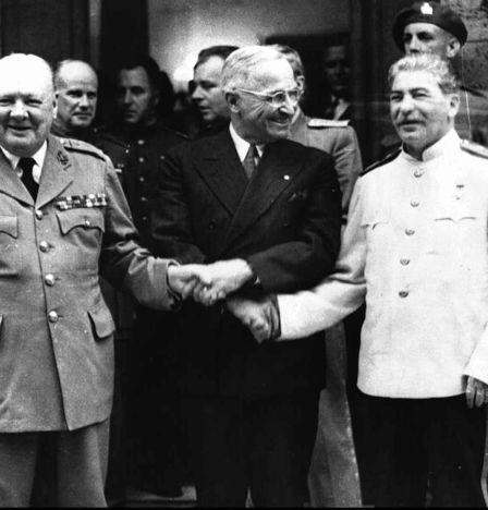 Les dirigeants des pays membres de la Grande alliance Winston Churchill, Joseph Staline et Harry Truman se serrent la main devant les photographes à Potsdam (Allemagne) en juillet 1945, en marge des négociations sur la configuration de l'Europe après la Seconde guerre mondiale