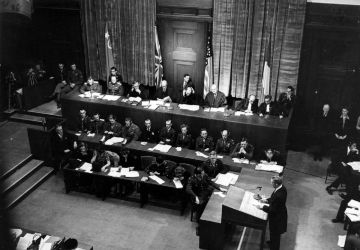 In the first session of the International Military Tribunal in the Palace of Justice in Nuremberg, Germany, Sydney S. Alderman (standing) of the U.S. prosecution panel reads the indictment which charges Hitler's former henchmen with war crimes. The photo shows the presiding judges in the background, sitting before the flags of Russia, Great Britain, the United States, and France