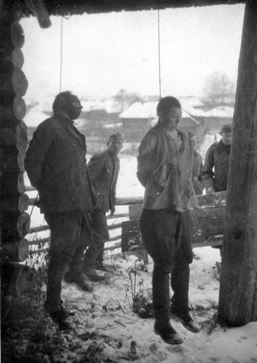 Des prisonniers soviétiques (un commissaire politique et un officier) exécutés dans le cadre de la mise en application du «Décret N°8» du 17 juillet 1941. Région de Novgorod, 1942. À partir de photographies prises sur des soldats capturés et tués de la Wehrmacht. Archives d'État de la Fédération de Russie / F. R-7021. Op. 128. D. 260. L. 9 ob. N° 1.