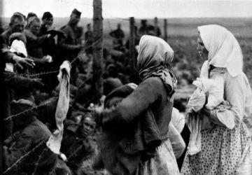 Des femmes passent des vêtements et de la nourriture aux prisonniers par-dessus le fil barbelé dans un camp de rassemblement de prisonniers de guerre. Bely (région de Kalinine). 1942. Archives de l'État russe de documents cinématographiques et photographiques (RGAKFD) / Op. 2, N° 46, sn. 22