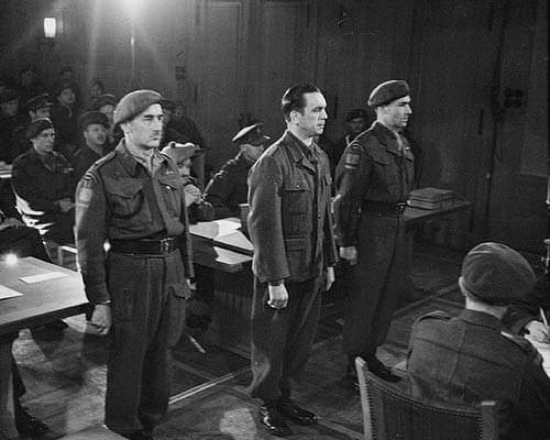 SS Brigadefuhrer Kurt Meyer standing in court with escorts Major Arthur Russel (left) and Captain Elton D. McPhail (right) in Aurich, Germany. 10 December 1945.