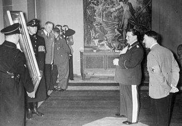 Adolf Hitler schenkt dem Reichsmarschall Hermann Göring (2R) ein wertvolles Gemälde zum 45. Geburtstag