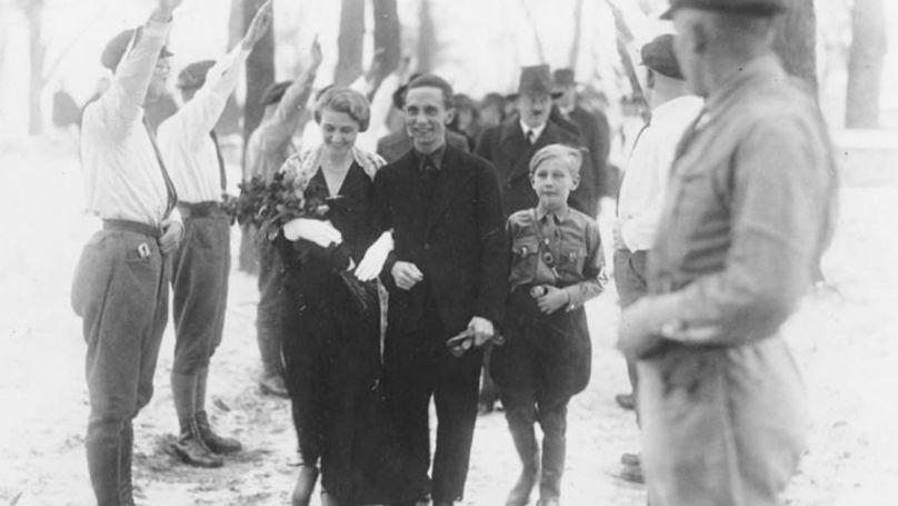 Le mariage de Joseph et Magda Goebbels. Les enfants des jeunesses hitlériennes saluent les jeunes mariés, le couple est suivi par leur témoin - Adolf Hitler, le 31 décembre 1931 / Bundesarchiv, Bild 183-R32860 / Auteur inconnu / CC-BY-SA 3.0