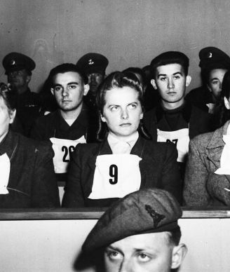 Irma Grese, leader of the women's Waffen SS at Belsen and assistant to Josef  Kramer, the Beast of Belsen, seen wearing placard no. 9 on her chest, during the War Crime Trials at Lueneburg, Germany, Sept. 17, 1945. Wardens at Belsen Hertha Ehlert, wearing no. 8 and Ilse Lithe, no. 10, sit either side of Irma Grese.
