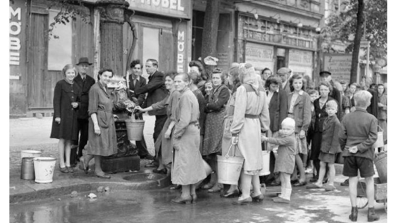 Des civils allemands font la queue à une pompe à eau dans une des rues de Berlin. Ces pompes constituaient la seule source d'eau potable dans la capitale allemande en raison de la destruction d'une grande partie du réseau de distribution.