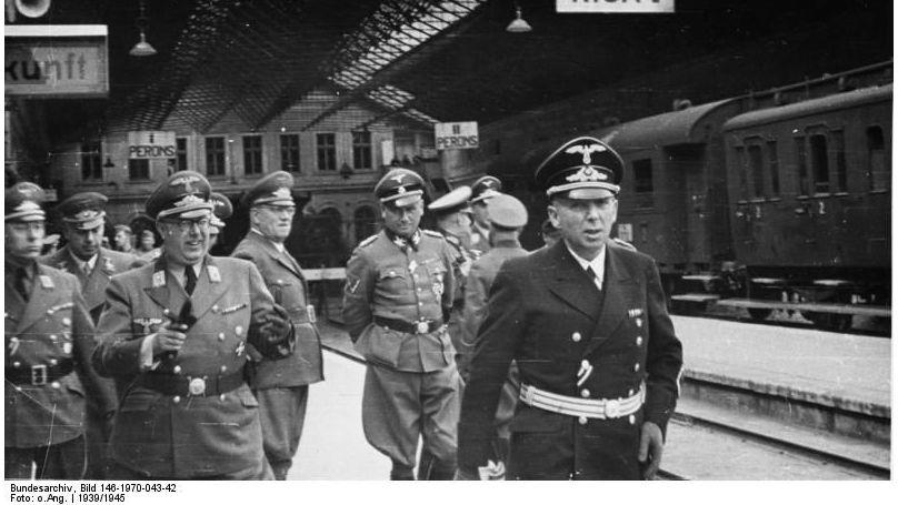 Friedrich Jeckeln (cinquième en partant de la gauche, les mains dans le dos) avec le commissaire général du commissariat du Reich des territoires de l'Est (Reichskommissariat Ostland) Hinrich Lohse (troisème en partant de la gauche) et un groupe d'officiers dans la gare de Riga (Lettonie), en février 1944. / Bundesarchiv, Bild 146-1970-043-42 / Fotograf: unbekannt / CC-BY-SA 3.0