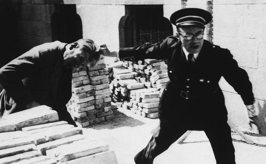 Un gendarme français sort un collaborateur de sa cachette et le traîne au poste de police. Rennes, le 6 août 1944