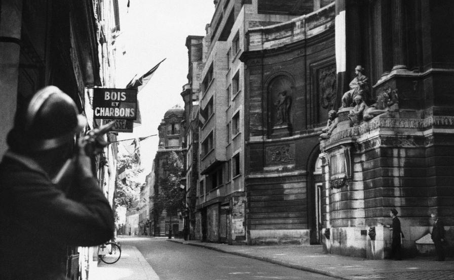 Un soldat français tire sur un sniper allemand qui se cache sur le toit d'un immeuble. Paris, le 26 août 1944
