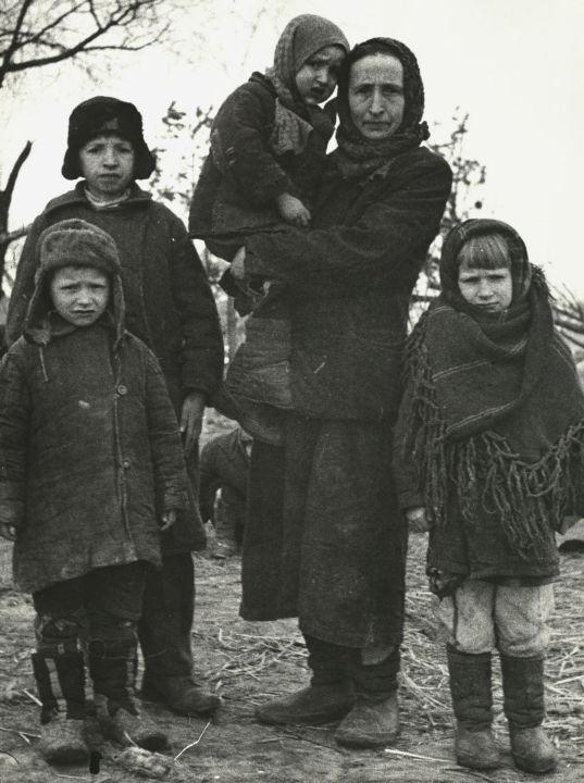 """Samuil Roisman:  """"Alle Menschen, die die Züge verließen, wurden sofort in zwei Gruppen aufgeteilt: Männer getrennt, Frauen und Kinder ebenfalls getrennt. Alle mussten sich sofort ausziehen, und wer sich sträubte, wurde von den Deutschen mit Stöcken verprügelt. Die Arbeiter, die dort ihre 'Pflichten' erfüllten, sammelten sofort die ganze Kleidung und trugen sie in die Baracken. Also mussten die Menschen den Weg bis zu den Gaskammern nackt gehen.""""   Smirnow: """"Ich muss Sie bitten, dem Gericht zu erzählen, wie die Deutschen diesen Weg zu den Gaskammern nannten.""""  Roisman: """"Dieser Weg hieß 'Himmelfahrt'.""""  Smirnow: """"Also quasi der Weg in den Himmel?""""  Roisman: """"Ja (…).""""  Smirnow: """"Sagen Sie bitte: Wie lange lebte ein Mensch noch, nachdem er in Treblinka eingetroffen war?""""  Roisman: """"Das ganze Verfahren – das Ausziehen und der Weg in die Gaskammer – dauerte acht bis zehn Minuten für die Männer und etwa 15 Minuten für die Frauen. Für die Frauen waren das 15 Minuten, weil ihnen auf dem Weg zur Gaskammer noch die Haare abgeschnitten wurden.""""  Smirnow: """"Warum wurden ihnen die Haare abgeschnitten?""""  Roisman: """"Die 'Herren' waren der Auffassung, dass diese Haare zur Herstellung von Matratzen für deutsche Frauen dienten sollten. (…) Als die Menschen aus den Zügen stiegen, hatten sie tatsächlich den Eindruck, sie würden sich in einer guten Station befinden, so dass sie weiter nach Suwalki, Grodno, Wien usw. fahren könnten."""""""