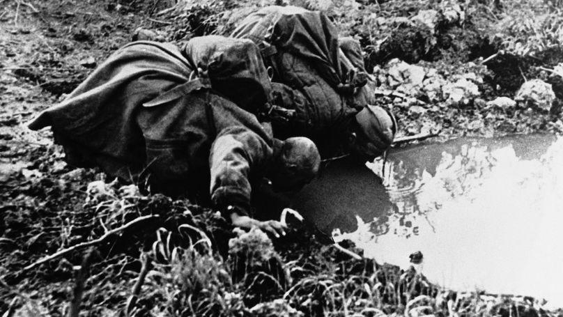 Les prisonniers de guerre soviétiques boivent à partir d'une flaque formée dans un cratère laissé par un obus, juillet 1942
