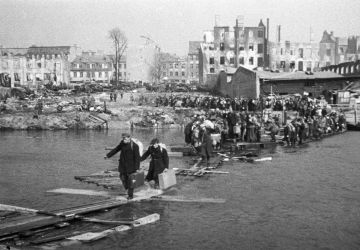 Residents of Königsberg cross the river using a wooden bridge as they return home on 9 April 1945