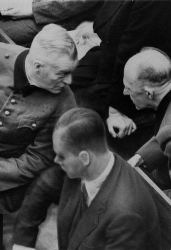 Gen. Alfred Jodl (right) and Gen. Wilhelm Keitel twist around to have a conference in the defendants box during the second day of the trials in Nuremberg, Germany, Nov. 21, 1945.