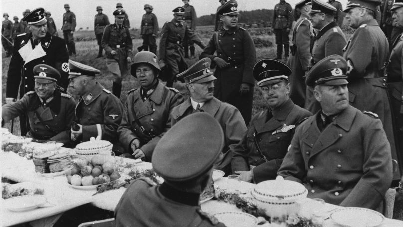 Adolf Hitler is surrounded by his aides, all of them high in the German Reich, during a field meal near Eger, Czechoslovakia, Oct. 3, 1938.