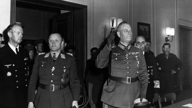 In this image provided by the U.S. Signal Corps, three high German officials emerge from a room after Germany's unconditional surrender terms were formally ratified in Berlin, May 9, 1945. Left to right: Col. Gen. Paul Stumpff, Luftwaffe commander; Field Marshal Wilhelm Keitel, German army commander (raising sword); and Gen. Adm. Hans von Freideburg (rear), commander of the German navy. (AP Photo/U.S. Signal Corps)