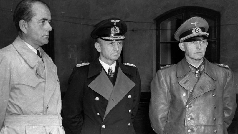 """Members of Germany's """"Doenitz'"""" government, Minister for Armaments and War Production Albert Speer, left, Grand Admiral Karl Doenitz, centre, and Gen. Alfred Jodl wait in a courtyard in Flensburg, Germany, after their arrest by British troops, May 24, 1945."""