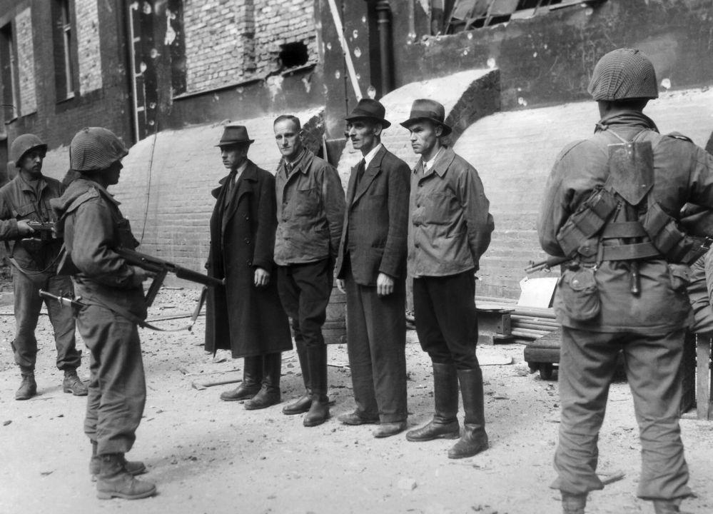 Nuremberg. Des soldats américains gardent un membre de la SS et trois agents de la Gestapo vêtus en civil, le 12 mai 1945