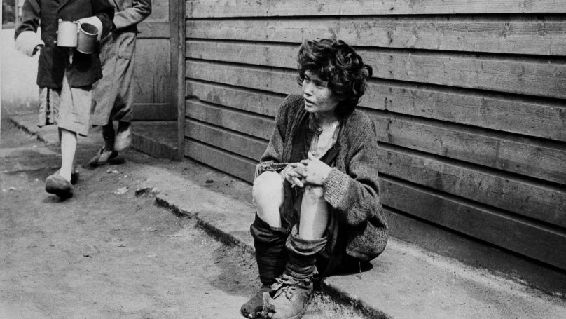Outside of one of the hutments, a woman sits dishevelled, while others in the background go for water in rusty tins in the Belsen Concentration Camp, Belsen, Germany, April 20, 1945.