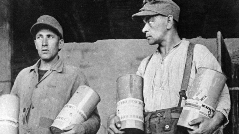 Des gardiens du camp de Majdanek montrent des  boîtes contenant du gaz toxique Zyklon-B (ils ont été pendus suite à la décision du tribunal en 1944 à Lublin, en Pologne).