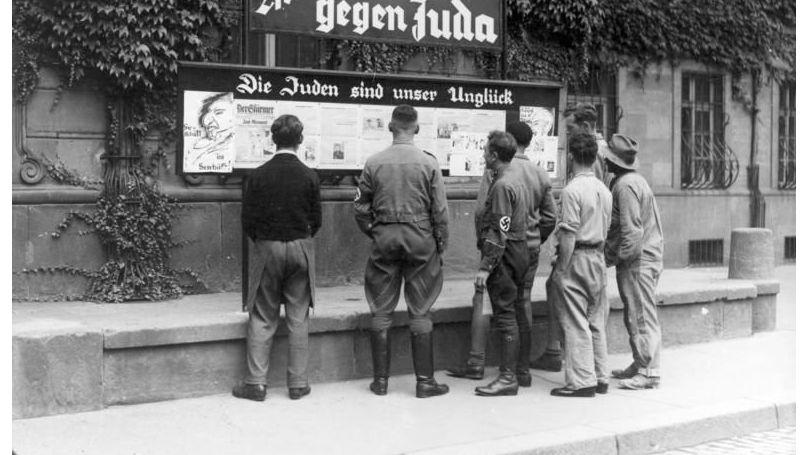 Des passants lisent le journal Der Stürmer // Bundesarchiv, Bild 133-075 // CC-BY-SA 3.0