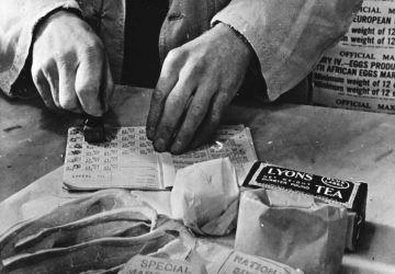 Rationnement des civils au Royaume-Uni: un vendeur tamponne des coupons alimentaires dans un carnet d'alimentation d'une ménagère britannique, 1943