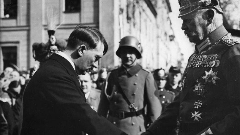 Le chancelier Adolf Hitler et le Président du Reich Paul von Hindenburg se serrent la main lors de la journée de Potsdam, la cérémonie officielle marquant l'ouverture de la nouvelle période de session du Reichstag de l'Allemagne nazie, le 21 mars 1933 // Bundesarchiv, Bild 183-S38324 / CC-BY-SA 3.0
