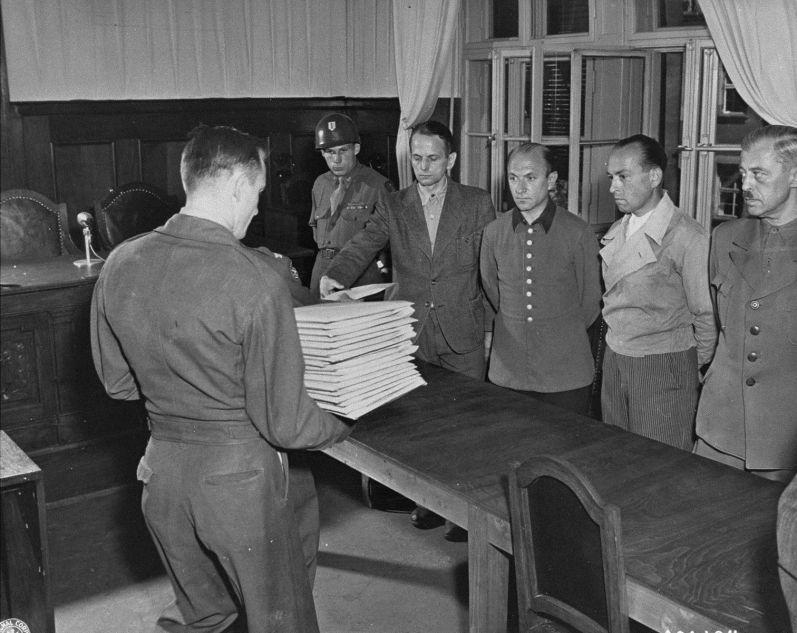 Les accusés (de gauche à droite: Otto Ohlendorf, Heinz Jost, Erich Naumann et Erwin Schulz) reçoivent les actes d'accusation. Juillet 1947 / USHMM