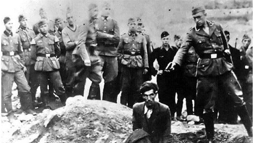 Un membre d'un Einsatzgruppe s'apprête à exécuter un homme devant une fosse commune à Vinnytsia, 1942. Une inscription au revers de la photo indique: «Le dernier Juif de Vinnytsia»