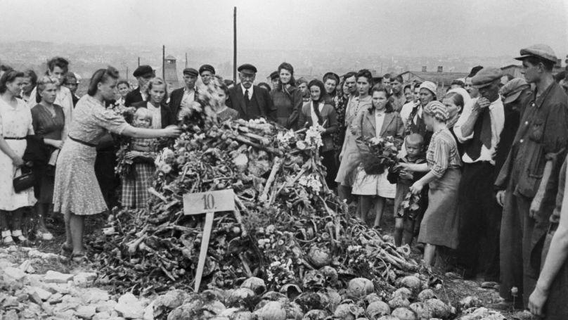 Le camp de concentration de Majdanek après la libération. Des habitants apportent des fleurs vers les restes des prisonniers.