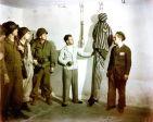 D'anciens détenus de Buchenwald font une démonstration de crochets de suspension et d'autres dispositifs de torture à des soldats américains. Ardean R. Miller.