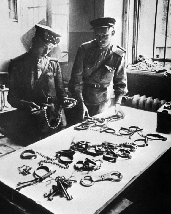 Des soldats soviétiques examinent des instruments de torture dans la prison de la Gestapo à Berlin, 1er juin 1945.